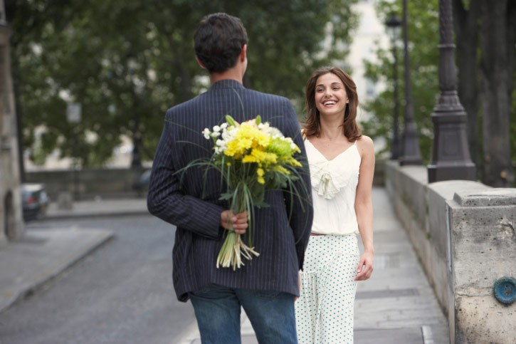 man gives flowers to woman in paris