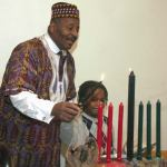 Clay Benson and his grandson lit a candle signifying the first day of the seven day Kwanzaa Community celebration held at the Wisconsin Black Historical Society. Sunday, Dec. 26 was the first day, which is Umoja-Unity of the seven day of principles for the holiday. The event was free and open to the public. (Photo by Robert A. Bell)
