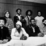 "Pictured at a 1976 press conference at the First Baptist Church in Raleigh, NC- (l to r, seated): Rev. Dr. Benjamin Chavis, Jr., William ""Joe"" Wright, Jr., Connie Tindall, Jerry Jacobs. (l to r, standing): Wayne Moore, Anne Sheppard, Willie ""Earl"" Vereen, James McKay, Marvin Patrick and Reginald Epps."