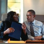 Congresswoman Gwen Moore (D-WI) discusses a matter with President Barack Obama as the two travel aboard Air Force One. (White House photo).