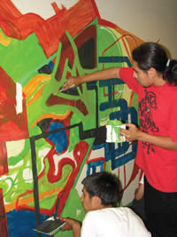Young people participate in creating a mural as an art project with SDC's Youth programs