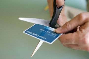 Hands cutting credit card with scissors