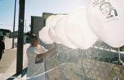 Luis Marquez ties balloons to a fence nearby as part of the conference.