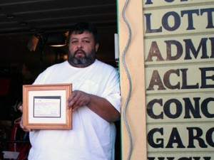 José Guzmán holds his business license outside the sporting goods shop he runs out of his garage.