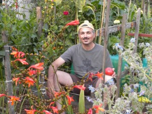 Marko Serpas relaxes in his plot at Dearborn Community Garden after harvesting tomatoes. Photo BRYAN GIBEL