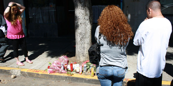 Community residents visit memorials for the two victims.