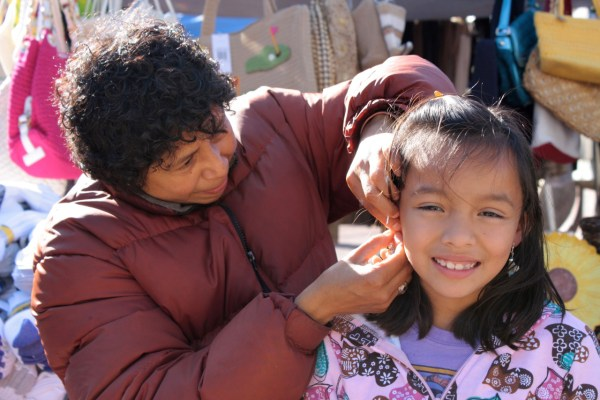 Diana Medina helps her little customer with her earrings.