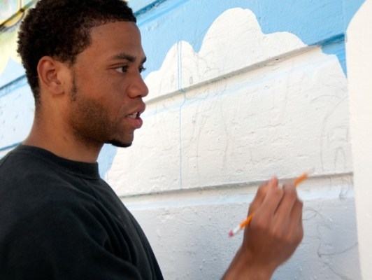 "Artist Uzomah ""Uzz"" Chiagoroh worked on the community mural on Bartlett."