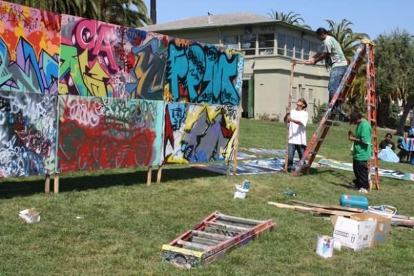 Ramon Miranda-Elisondo, Suaro Luis-Cervantes and Alex Elizondo build a community wall donated by Precita Eyes to be painted on by park goers.