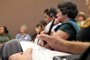 One neighbor takes notes as others listen to the proceedings, some with special headsets for Spanish translation.