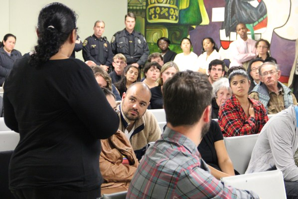 Audience members look on as Susana Roja addresses the crowd at the Good Samaritan Family Resource Center Monday night.