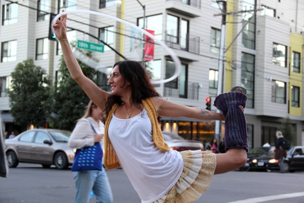 Dani Bobbi Lee, 27, performs yoga with a hula hoop at the corner of 18th and Valencia Street, Photo by Mission Local staff.