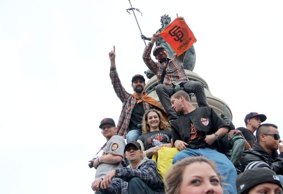 Fans climb everything in sight to watch the parade. Photo by Chelsi Moy.