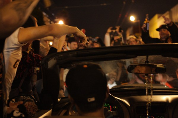 A man is mobbed by fans as he drives on Mission Street. Photo by Rigoberto Hernandez