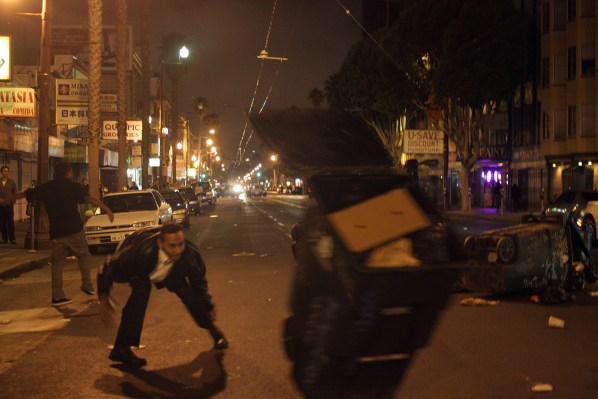 A man throws a garbage can to the street. The can was later set on fire. Photo by Rigoberto Hernandez