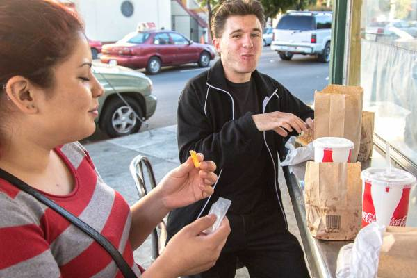 James Cowen chews on a Burger-Burger while his friend and co-worker and Melina Rosales eats a cheeseburger. They spent their break from work dining at Whiz Burgers and spent about $10 each on a meal of hamburger, fries and soda.