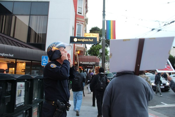 An SFPD officer yells among protestors to other cops during a march in support of World Homeless Action Day. Photo by Carly Nairn.