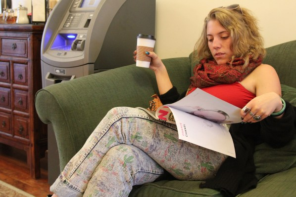 "A young woman enjoys her coffee while reading ""Nylon"" magazine at Borderlands Cafe."