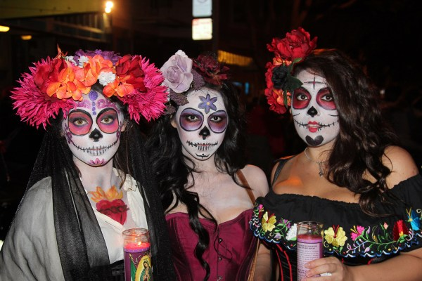 Three ladies decked out in Dia de los Muertos outfits attend the parade.