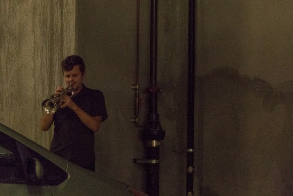 A man plays a trumpet in a cavernous Walgreens parking lot.