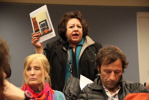 A lady holds up SFMTA's guide on various parking management solutions used by agency throughout San Francisco.