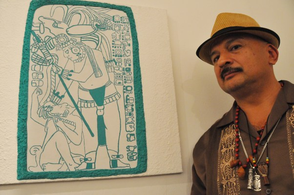 Roberto Y. Hernandez, lead artist and instructor, poses next to art made by one of his students. Photo by Alejandro Rosas.