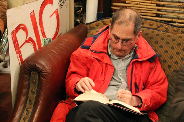 A man reads on the couch of Adobe Bookshop before the readings by well-known authors begin. Photo by Molly Oleson