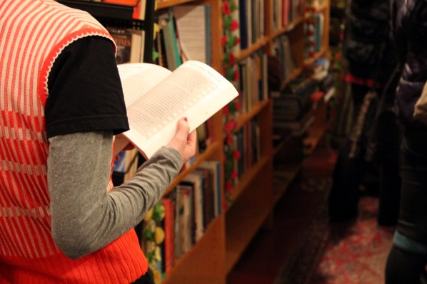 "A young woman flips through a book on the night of ""A Celebration of the Adobe Bookshop."" Photo by Molly Oleson"