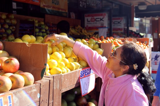 A woman looks for fruit on Mission Street.