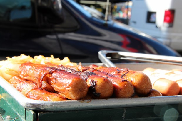 A bacon wrapped hot dog sizzles on Mission and 23rd St.