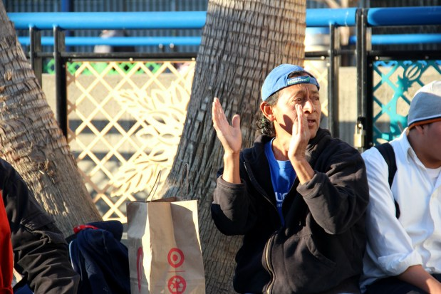 A man claps to music being played at the 16th Street BART Station. Photo by Molly Oleson
