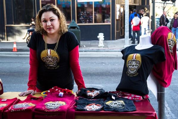 Ana Manzanares de Mixcoatl Arts and Crafts vendiendo playeras de los 49ers afuera de su tienda. Su socia, Connie Rivera comentó que el día era perfecto para promover su negocio. Foto de Marta Franco