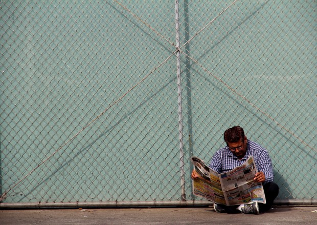 A man reads a newspaper on Folsom Street.