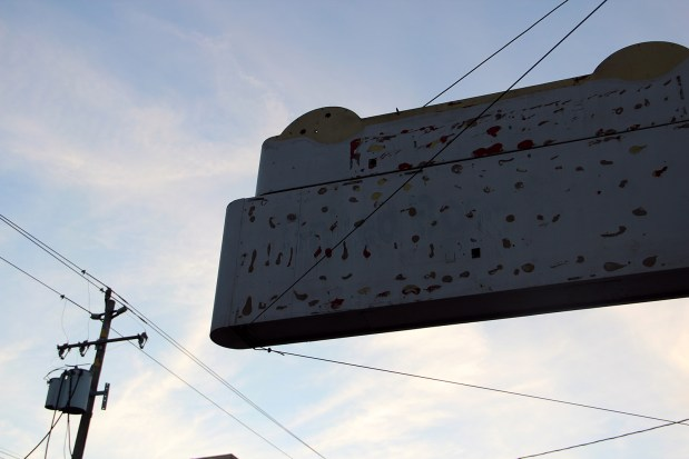 An old sign, a telephone pole and some wires create eye-catching shapes against a fading blue sky.