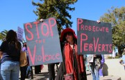 A woman holds signs in support of a rally to stop violence against women.
