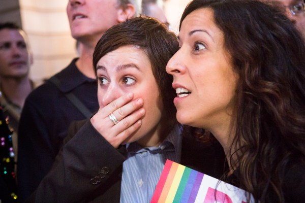 Lori Bilella and Renata Moreira look stunned after the ruling on DOMA was announced. Photo by Marta Franco.