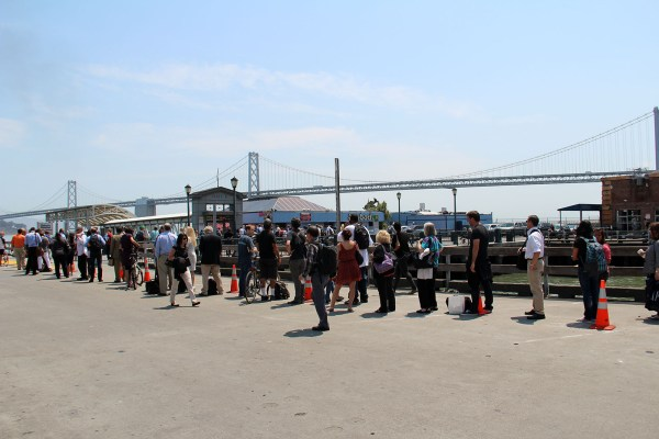 People line up for a ferry headed to the East Bay. The Bay Bridge can be seen in the distance.