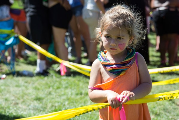 A girl waits behind the security tape in front of he stage.