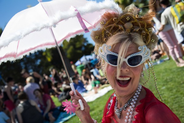 A woman smiles as she walks under the sun at Dolores Park during 2013's Pride . Photo by Marta Franco.