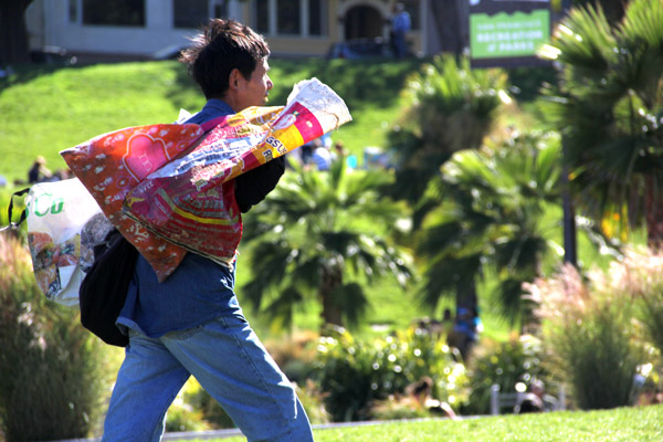 A man crosses Dolores Park with bags full of plastic bottles to recycle.
