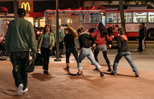 A four-women dance group, which invited performers, do an explosive dance around the perimeter of the plaza. Here they dance down Mission Street.