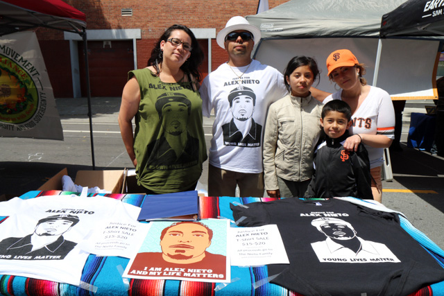Benjamin Bac Sierra and family selling Justice for Alex Nieto t-shirts and posters.  Photo by Claire Weissbluth