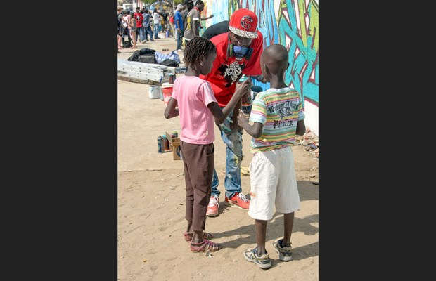 Wall #1: Young Senegalese graffeur and university student Kromagnon introduces some neighborhood children to spray paint.