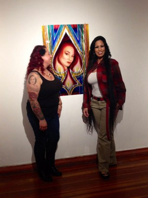Women pose in front of portrait by Adolfo Arias