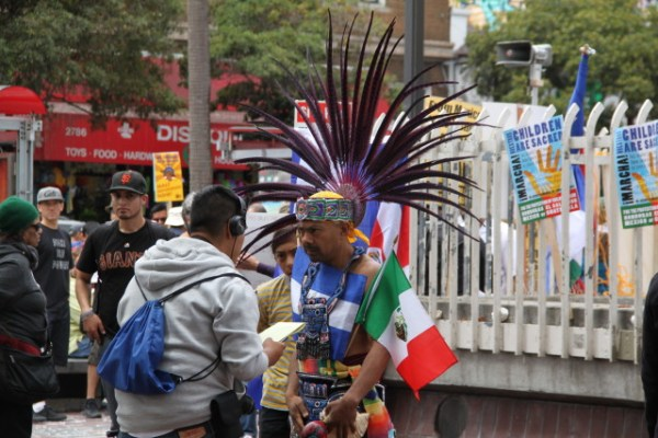 A man in native attire sports an impressive mohawk, and brandishes the flags of Mexico and El Salvador. Photo by Joe Rivano Barros.