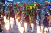Flowers and votives placed on memorial site for Rashawn Williams. Photo by Daniel Hirsch.