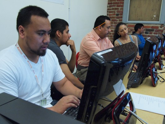 Leo Sosa (center) helps the Mission Techies keep track of their progress servicing computers from schools and community members.