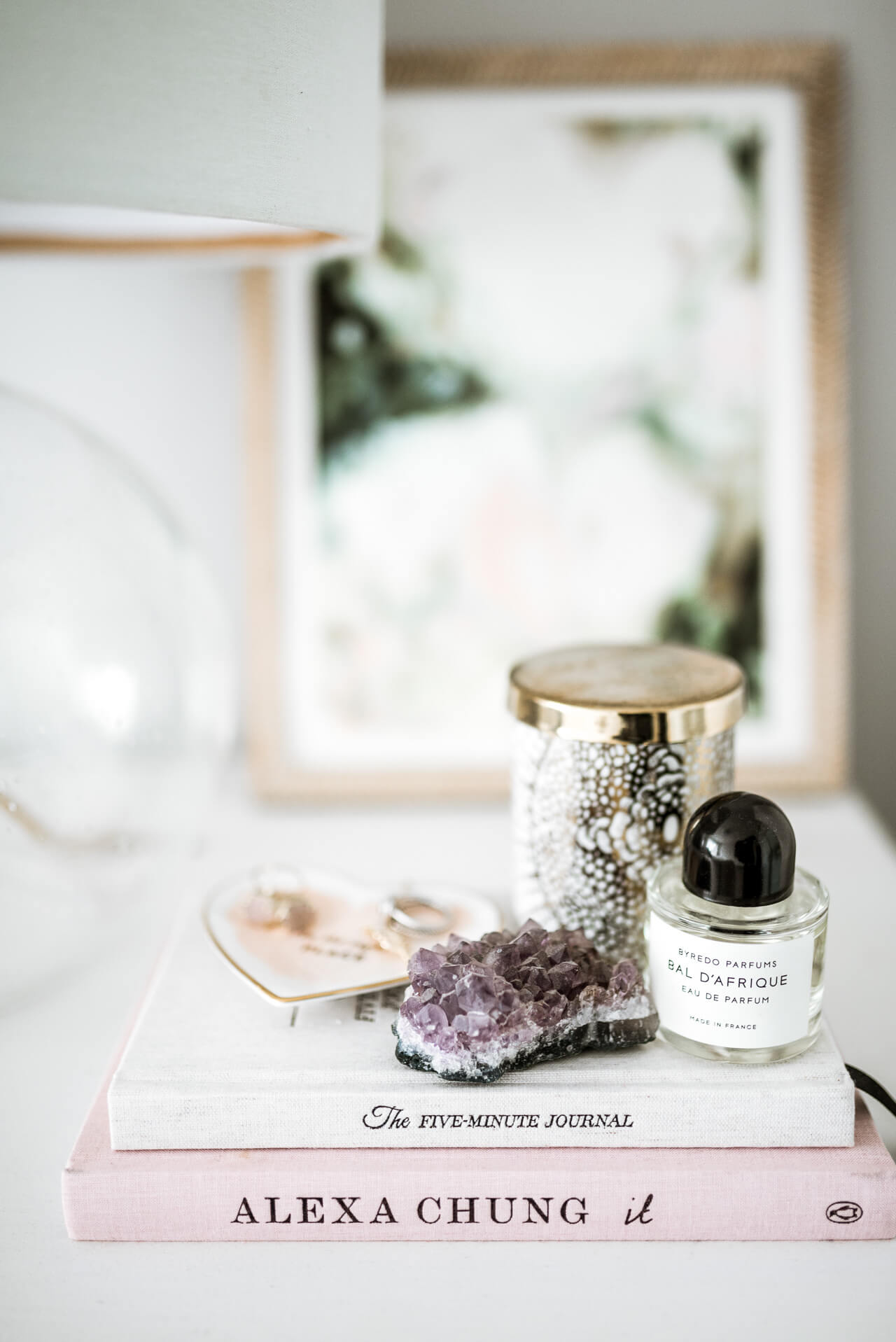 bedside table styling with candle and perfume