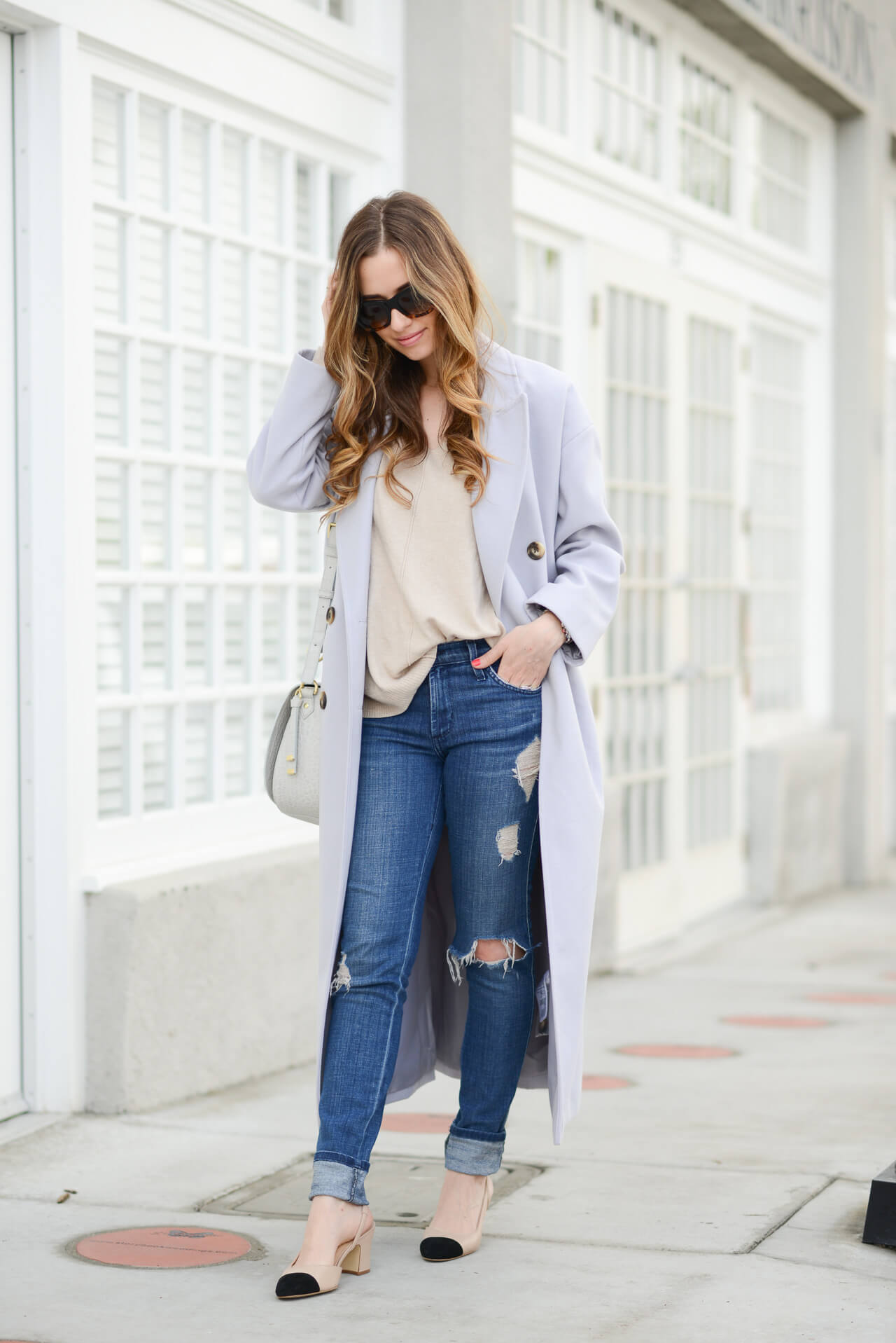 lavender coat with tan sweater and distressed jeans