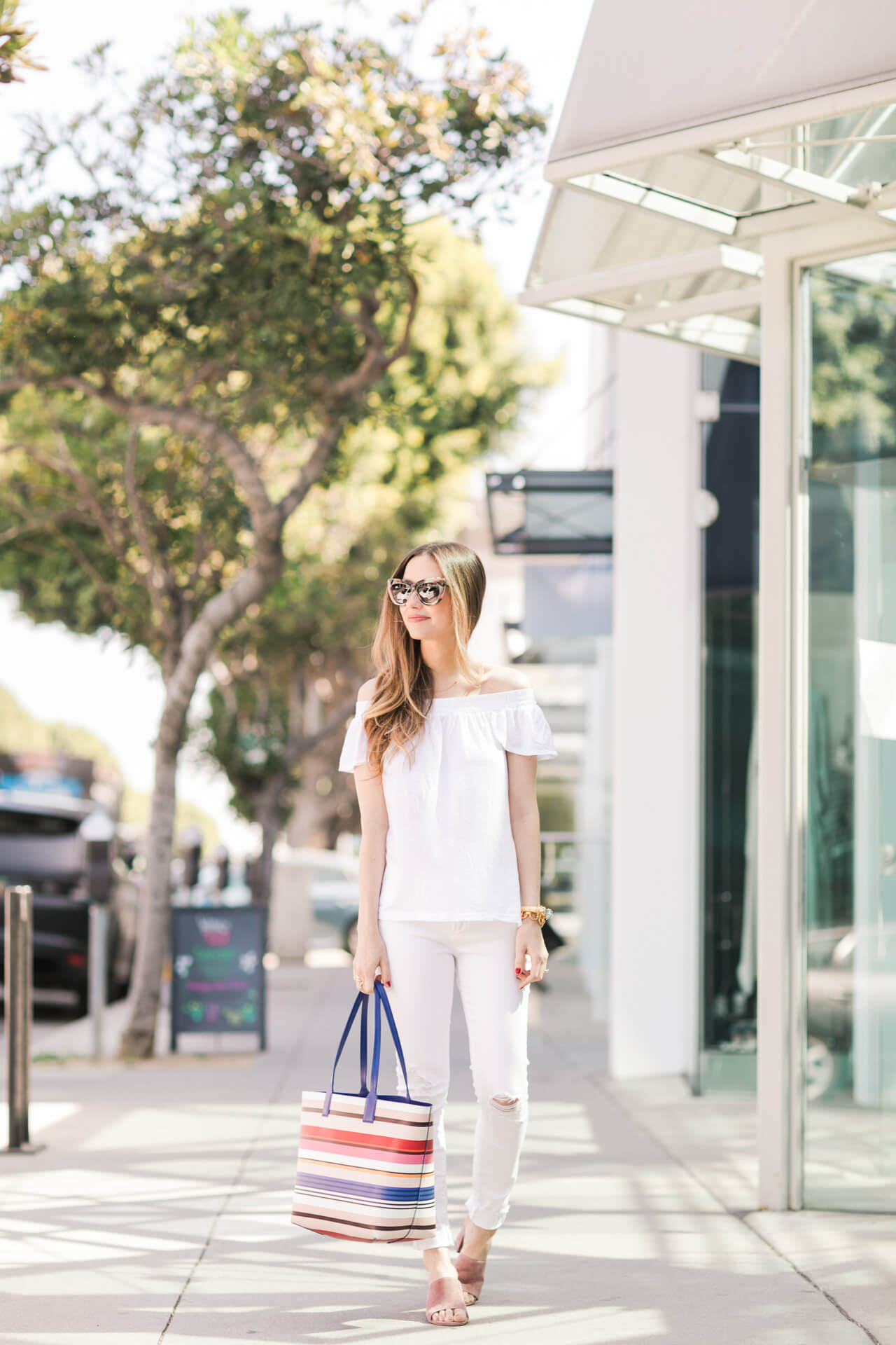 all white outfit for spring with a striped tote bag and pink mules